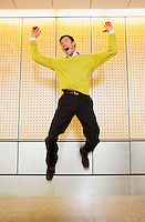 A early 30's Caucasian man in casual business attire jumps enthusiastically into the air with his hands over his head.20050916_PR_A.20050916_MR_D