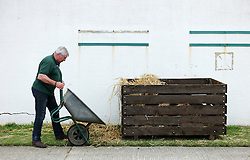 © Licensed to London News Pictures.14/07/15<br /> Harrogate, UK. <br /> <br /> A man empties out a wheelbarrow after cleaning his cattle pen on the opening day of the Great Yorkshire Show.  <br /> <br /> England's premier agricultural show opened it's gates today for the start of three days of showcasing the best in British farming and the countryside.<br /> <br /> The event, which attracts over 130,000 visitors each year displays the cream of the country's livestock and offers numerous displays and events giving the chance for visitors to see many different countryside activities.<br /> <br /> Photo credit : Ian Forsyth/LNP