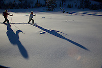Russell Laman (age 12) and Jessica Laman (age 9)  cross-country skiing below the Teton Range, casting long shadows in the afternoon light.<br />