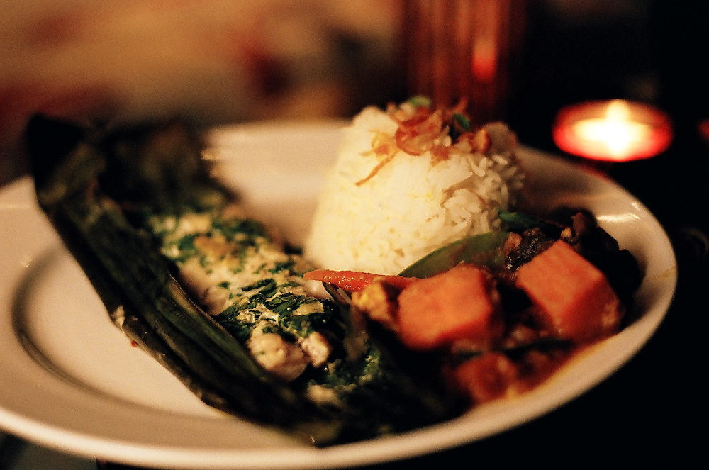 Asian Fusion Cuisine Dinner Party Food - Banana Leaf Fish, Sticky Rice, and Curried Vegetables.
