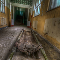 An abandoned Soviet sports hospital in East Germany with canvas stretcher on floor in hallway