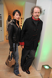 ROSEY CHAN and MIKE FIGGIS at an exhibition of photographic portraits by Bryan Adams entitled 'Hear The World' at The Saatchi Gallery, King's Road, London on 21st July 2009.