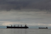 Views from Jericho Beach across the Burrard Inlet of the Salish Sea, Vancouver; here some empty cargp ships wait in the inlet before going into the Port of Vancouver