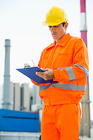 Male architect in protective workwear writing on clipboard at site