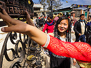 """04 MARCH 2017 - KATHMANDU, NEPAL: Women spin prayer wheels at Swayambhu Stupa in Kathmandu. The temple is also known as the """"monkey temple"""" because of the number of macaques that live there.     PHOTO BY JACK KURTZ"""