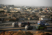 Buses heading north from Karachi pass in front of Sohrab Goth, a predominantly Pakhtun slum from where wanted militants have been arrested, near Karachi, Pakistan.