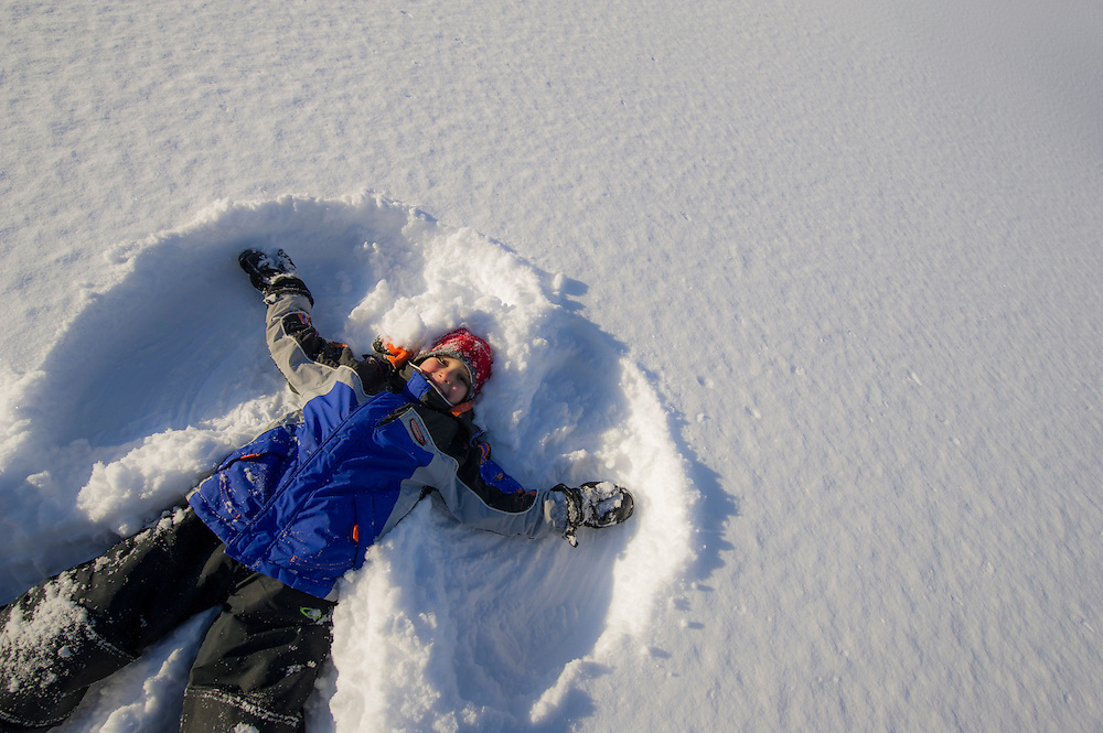 A young boy making a snow angel in deep fresh snow.