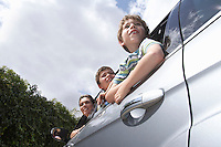 Mother and two boys (5-11) leaning out car window low angle view