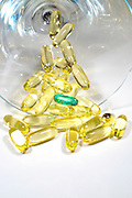 Several yellow gelatin pills with one unique green one on white background