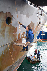 Man sitting on a winch and painting the hull of a ship; Las Palmas; Canaries,