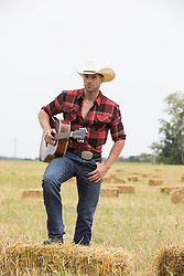 cowboy in a field holding a guitar