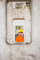 View of male architect through pillars at construction site