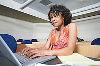Female student using laptop in lecture theatre