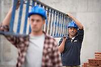 Two construction workers carrying ladder