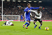 Leicester City midfielder Demarai Gray (7) battles with Fulham midfielder Jean Michael Seri (24) as Fulham defender Maxime Le Marchand (20) lies on the ground during the Premier League match between Fulham and Leicester City at Craven Cottage, London, England on 5 December 2018.