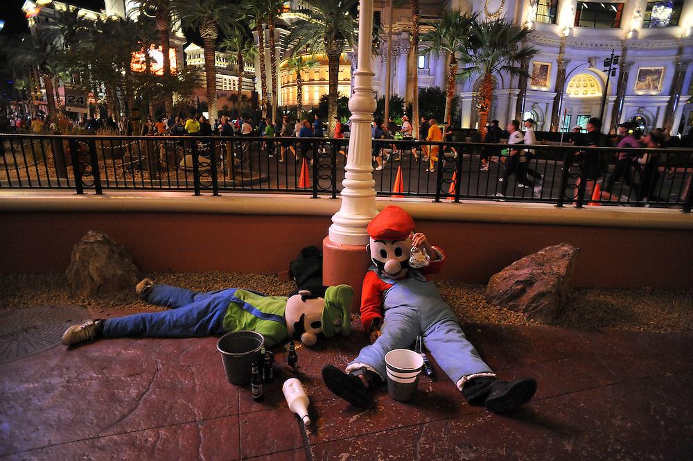 Actors posing as Mario and Luigi work for tips on Las Vegas BLVD as the Vegas Marathon streams past them.