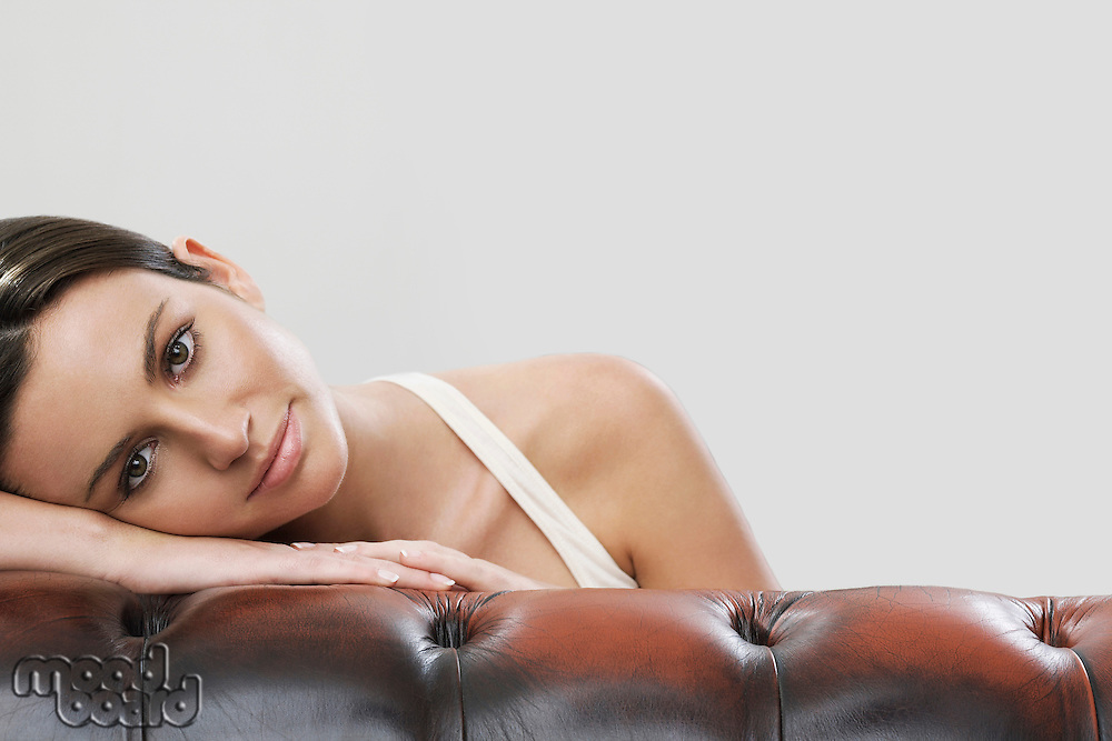 Portrait of woman leaning on sofa against gray background