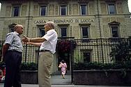 Two men talking outside the Cassa Di Risparmio De Lucca in Italy ..., Travel, lifestyle