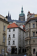 A view of Prague Castle peaking through the Little Quarter of Pargue, Czech Republic. The castle, first constructed in the 10th century is the seat of government in the Czech Republic.