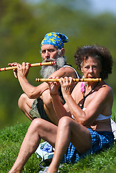 A couple enjoy playing their flutes in the sunshine on a grassy bank by the Highgate Swimming ponds in London February 10 2018.