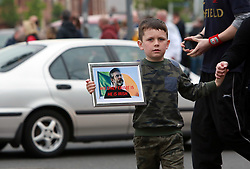 """A young boy carrying a picture of Gerry Adams attends a rally in west Belfast, Saturday, May 3rd, 2014. Several hundred people have been attending a rally demanding the release of Sinn FÈin leader Gerry Adams who has been arrested. Gerry Adams spent a third night in police custody in connection with the 1972 murder of mother-of-10 Jean McConville.West Belfast mother Jean McConville was abducted and murdered by the Provisional IRA and secretly buried on the beach. In 1999, the IRA finally admitted that it had killed McConville and eight others of the """"Disappeared"""". The IRA claimed she had been passing information about republicans to the British Army. Sinn Fein leader Gerry Adams has spent a third night in police custody in connection with the 1972 murder of mother-of-10 Jean McConville at Antrim PSNI Police Station in Northern Ireland. Picture by Paul McErlane / i-Images"""