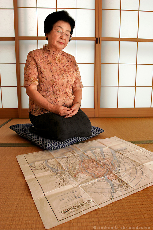 """Ms HIROKO KATAKEYAMA. Hiroshima A-Bomb survivor, siting in front of an old map showing the epicenter and the range or the A-bomb in the city of Hiroshima. Elementary school student who was four kilometers from the epicenter.  She lost many of her relatives in the bombing, including her cousin who was the same age.  We felt worn our and usually retreated to the barn, away from the quarreling adults.  One day my cousin confessed that his hair had started falling out.  I still vividly remember his blank face, frightened at this sign of death.  She still cries when she tells this story and is one of the few survivors who confesses to hating America. When she was invited by the UN to speak in New York two years ago, she almost didn't go. """"I couldn't bear the thought of going to the US""""."""