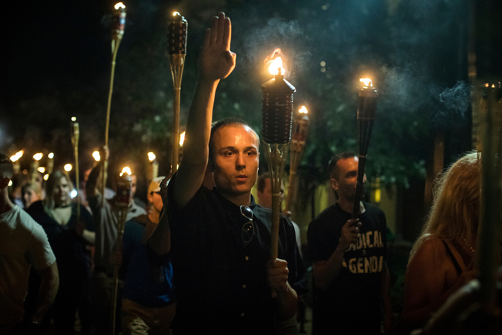 CHARLOTTESVILLE, VA. USA. August 11th 2017. Members or the Alt-Right led a torch march thru the grounds of the University of Virginia, the night before of the scheduled big rally. <br /> <br /> &quot;You will not replace us&quot; and &quot;Jews will not replace us&quot; were common chants during the march, as a few where giving the Nazi salute.<br /> <br /> The rally occurred amidst the backdrop of controversy generated by the removal of Confederate monuments throughout the country in response to the Charleston church shooting in 2015. The event turned violent after protesters clashed with counter-protesters, which combined with the subsequent vehicle-ramming attack left over 30 injured. (wikipedia)
