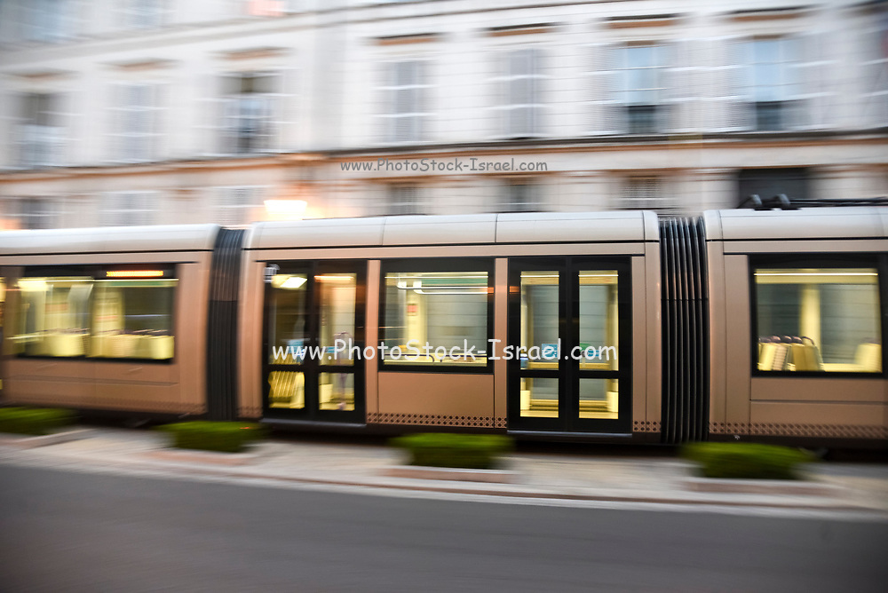 Speeding brown tram on Rue Jeanne d'Arc in Orleans, France