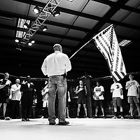 Jamie Houston, center, promoter of Summit Fighting Championships, holds an American flag during the playing of the National Anthem before the start of the MMA fight on Saturday, August 5th during the Summit Fighting Championships match at the Tupelo Furniture Market.