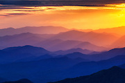 A colorful sunset over the Blue Ridge Mountains with the sky turning orange and red while sections of the mountains remained blue.
