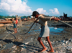 BANGLADESH CHITTAGONG MADHOM BIBIR HAT OCT00 - Labourers pull a steel cable through the mud. It is to be attached to giant pieces of metal cut loose from the ship's body - which will winch it on land for further dis-assembly...Several thousand labourers work on one medium-sized (50,000 ton) ship for a period of around three months, until it is completely dismantled and taken apart. ..Since Bangladesh does not possess mineral resources such as iron ore, it works out more cost-efficient to employ a large army of day-labourers to recycle the scrapped ships rather than to import ore. On average, a labourer can expect to earn a little more than 1 US Dollar per day...jre/Photo by Jiri Rezac..© Jiri Rezac 2000..Contact: +44 (0) 7050 110 417.Mobile: +44 (0) 7801 337 683.Office: +44 (0) 20 8968 9635..Email: jiri@jirirezac.com.Web: www.jirirezac.com..© All images Jiri Rezac 2000 - All rights reserved.