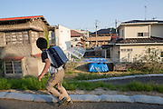 Pojke p&aring; v&auml;g hem fr&aring;n skolan. I en tr&auml;dg&aring;rd har det &ouml;versta str&aring;lningskadade jordlagret samlats under bl&aring; pressening i ett bostadsomr&aring;de i Fukushima City, Japan<br /> <br /> A boy on his way home from school. In a garden contaminated top soil is gathered underneath a blue tarp. Fukushima City, Japan
