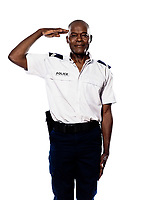 Portrait of an afro American police officer saluting in studio on white isolated background