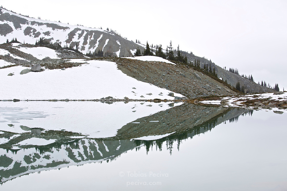 Mountain scenery reflected in perfectly still Blackcomb Lake, on Blackcomb Mountain, near Whistler, British Columbia, Canada.
