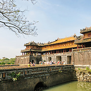 The bridge and Ngo Mon Gate at the Imperial City in Hue, Vietnam. A self-enclosed and fortified palace, the complex includes the Purple Forbidden City, which was the inner sanctum of the imperial household, as well as temples, courtyards, gardens, and other buildings. Much of the Imperial City was damaged or destroyed during the Vietnam War. It is now designated as a UNESCO World Heritage site.