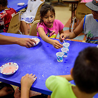 Philamina Torrez, left, reaches for a dropper of vinegar as she and other children experiment with vinegar, lemon juice, baking soda and other ingredients during the Fizzy Science workshop at the Gallup Children's Library Saturday.