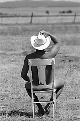 naked cowboy sitting on a chair on a ranch