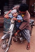 Father and child on a motorbike. Tenasserim district. Burma 2001