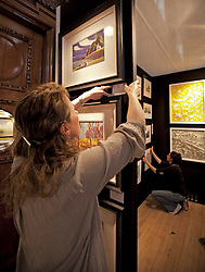 © Licensed to London News Pictures. 19/04/2012. London, U.K..Lucy Carty from Artshouse setting up at  The Chelsea Art Fair in Chelsea Old Town Hall where Around 35 galleries and dealers offer modern British and contemporary art for sale, including paintings, drawings, etchings and sculptures. Represents 500 international artists, with art worth up to £20k. The fair runs from 19th April - 22nd April..Photo credit : Rich Bowen/LNP