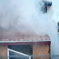 010214       Adron Gardner<br /> <br /> A opens a second-floor window to vent a house fire in Gamerco Friday.