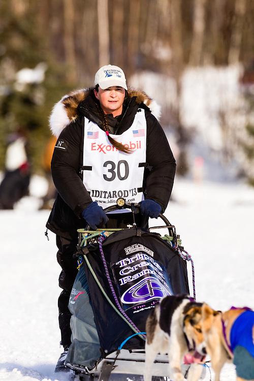 Musher Jessie Royer competing in the 41st Iditarod Trail Sled Dog Race on Long Lake after leaving the Willow Lake area at the restart in Southcentral Alaska.  Afternoon.