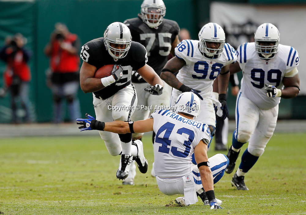 Oakland Raiders running back Michael Bush (29) runs over Indianapolis Colts safety Aaron Francisco (43) during the NFL week 16 football game against the Indianapolis Colts on Sunday, December 26, 2010 in Oakland, California. The Colts won the game 31-26. (©Paul Anthony Spinelli)