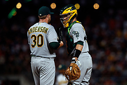 SAN FRANCISCO, CA - AUGUST 13: Dustin Garneau #3 of the Oakland Athletics talks to Brett Anderson #30 at the pitchers mound during the sixth inning against the San Francisco Giants at Oracle Park on August 13, 2019 in San Francisco, California. The San Francisco Giants defeated the Oakland Athletics 3-2. (Photo by Jason O. Watson/Getty Images) *** Local Caption *** Dustin Garneau; Brett Anderson