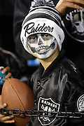 A young fan holds a football as he looks on with a silver and black painted face during the Oakland Raiders NFL week 12 regular season football game against the Kansas City Chiefs on Thursday, Nov. 20, 2014 in Oakland, Calif. The Raiders won their first game of the season 24-20. ©Paul Anthony Spinelli