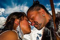 A Maori man with ta moko (facial tattoo) and woman doing hongi (traditional Maori greeting), Te Puia (New Zealand Maori Arts & Crafts Institute), Rotorua, New Zealand