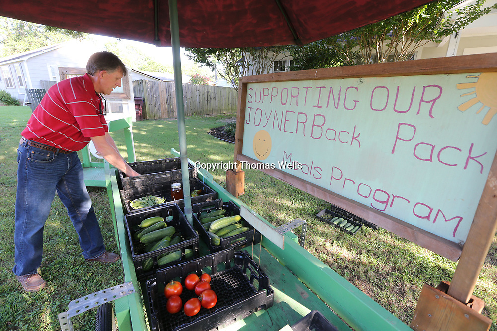 "Jerry Thompson begins setting up his ""veggie cart"" in front of his home on Long Street in Tupelo."