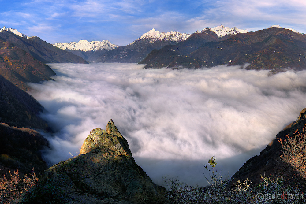 An unusual view of the valley of Susa completely filled up with fog, one of the many valleys of the western Alps in Piedmont. Taken from mount Pirchiriano on a cold morning at the end of November, this is stitched from four verticals.