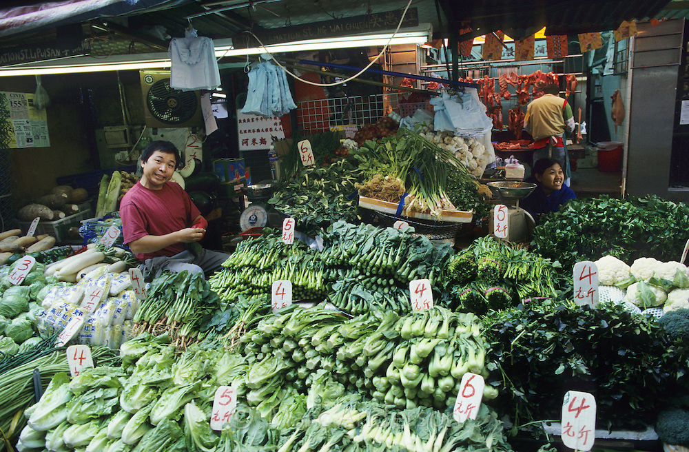 A man at a market stall selling chinese green vegetables, including bok choy, in Hong Kong, China.