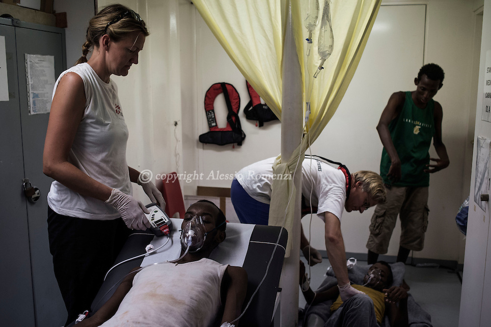 Italy: MSF Dignity1: MSF doctors Marte Ulvedal (L) and Tancred Stobe examine sick African migrants rescued at sea by Italian coast guard and then transferred on the Dignity1 on August 23, 2015. Alessio Romenzi