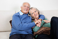 Portrait of happy elderly man with arm around spouse sitting on sofa at home